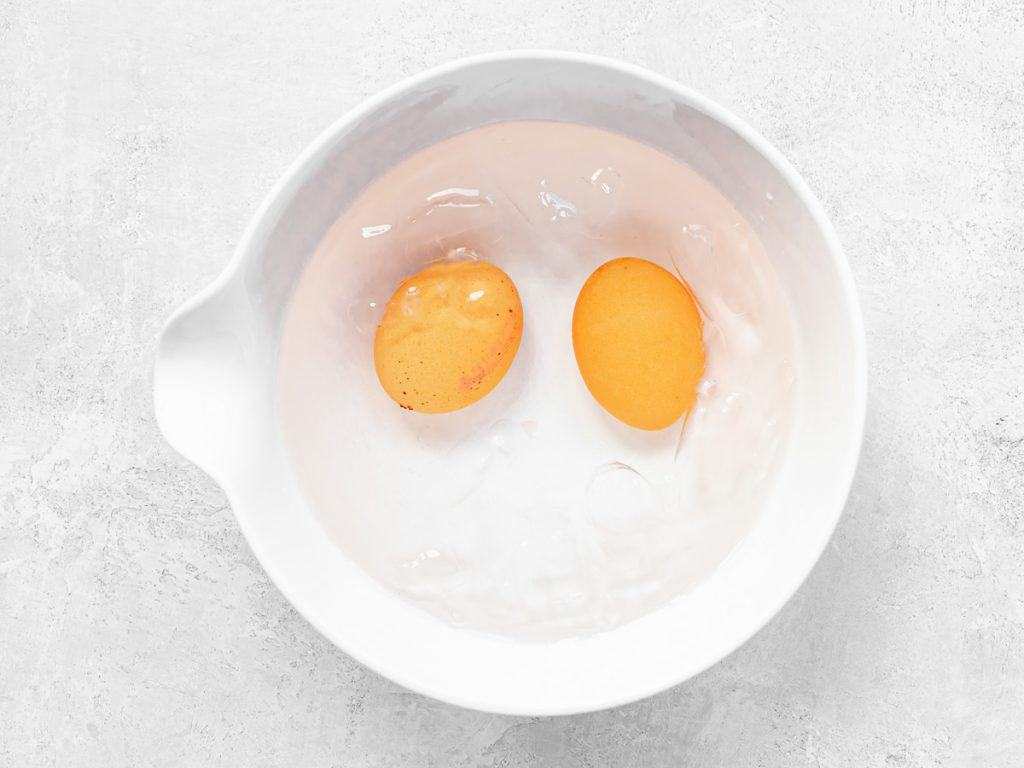 Two whole hard boiled eggs submerged in ice cold water in a white bowl