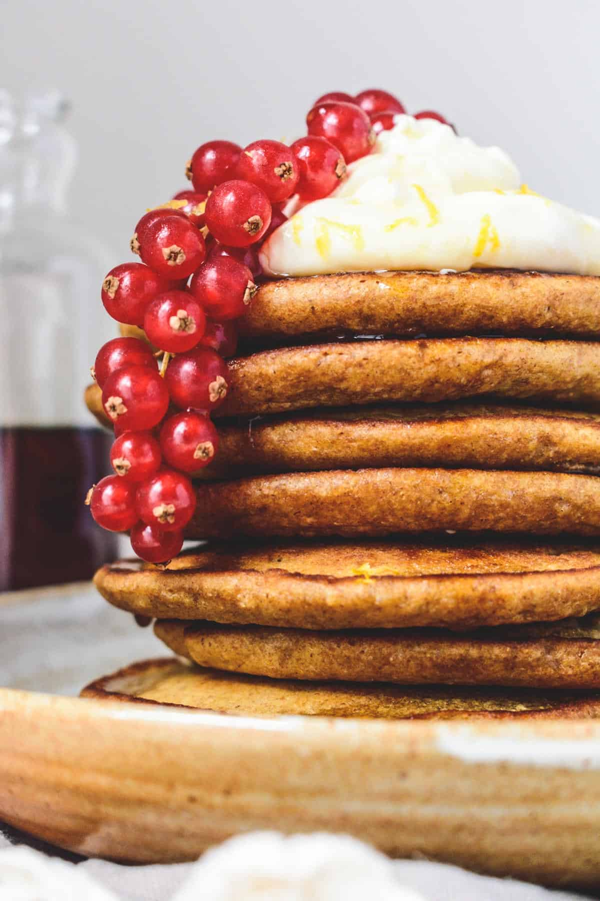 Stack of wholemeal ginger pancakes topped with lemon cream and redcurrants