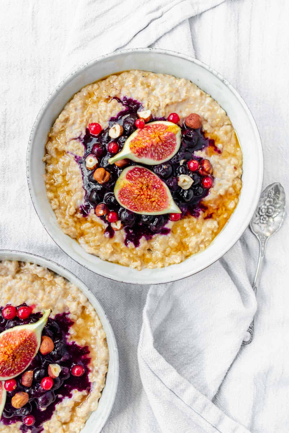 Two bowls of hazelnut porridge topped with blueberry sauce, figs and hazelnuts