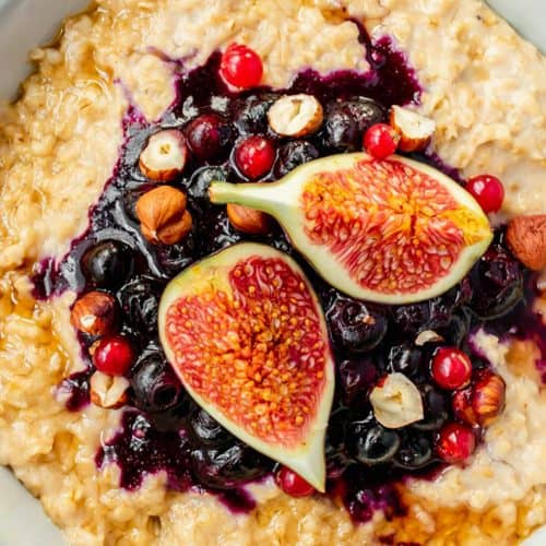 A bowl of hazelnut porridge topped with blueberry sauce, figs and hazelnuts