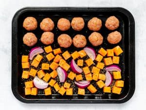 Turkey sausage meatballs on baking tray with sweet potatoes and onion wedges