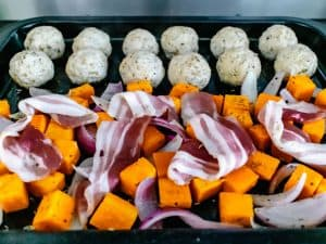 Half cooked turkey sausage balls and sweet potatoes on a baking tray with raw bacon