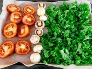 Tomatoes, mushrooms and kale on baking sheet