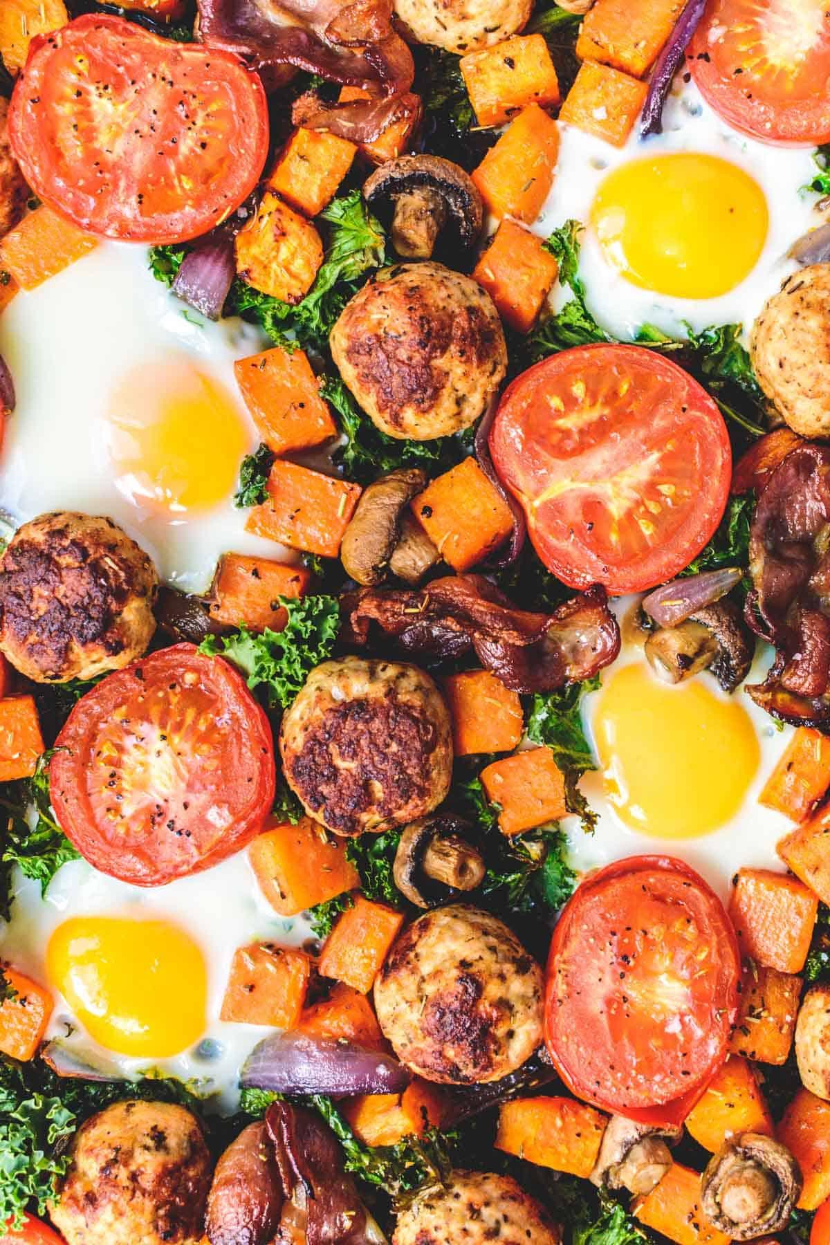Eggs, bacon, mushrooms, tomatoes, kale, turkey sausage on baking tray