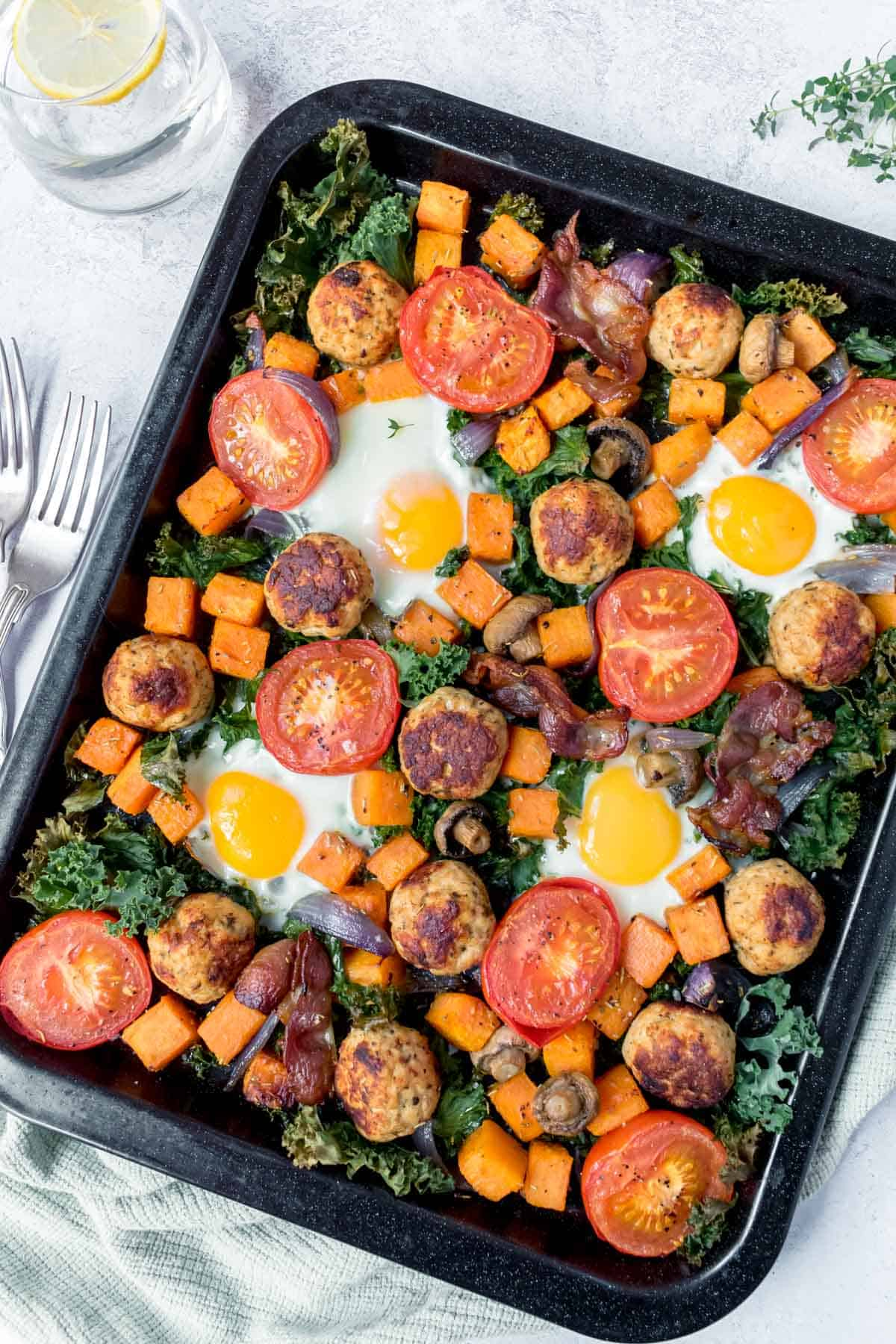 Healthy Full English Breakfast on a baking tray settled on a green tea towel with a glass of water and two forks